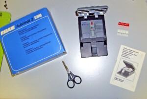 Revue Automat 2 (Trockenklebepresse) mit Packung und passenden Folien